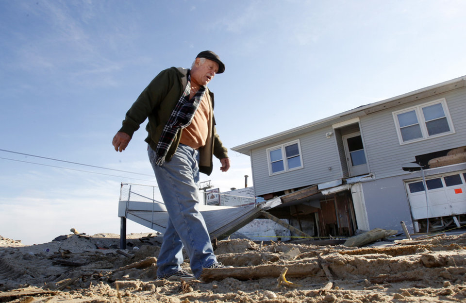 Photo - Henny Mauro walks in Seaside Heights, N.J., Thursday, Jan. 3, 2013,  past a beach-side home that was destroyed by Superstorm Sandy.  Under intense pressure from angry Republicans, House Speaker John Boehner has agreed to a vote this week on aid for Superstorm Sandy recovery.  (AP Photo/Mel Evans)