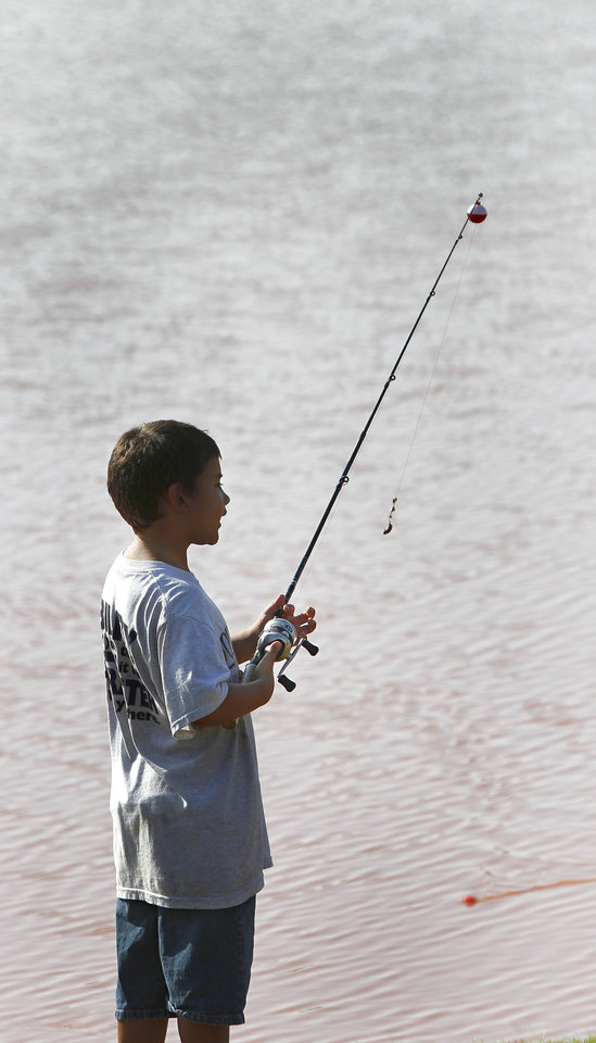 Photo - Gabriel Hernandez, 10, came to the pond in Buck Thomas Park to fish for the first time.  Gabriel and his younger brother, Adriel, 8, both learned the basics of fishing at the derby. Moore hosted its annual kids fishing derby Saturday morning, July 27, 2013,  at Buck Thomas Park.  As part of the event this year, a charity called the Tackle the Storm Foundation handed out rods and reels to tornado victims. Several bass fishing pros from Oklahoma attended the event to help distribute the fishing equipment and share fishing tips with the young anglers. An event official  said about 250 children participated in the fishing derby. Photo  by Jim Beckel, The Oklahoman.