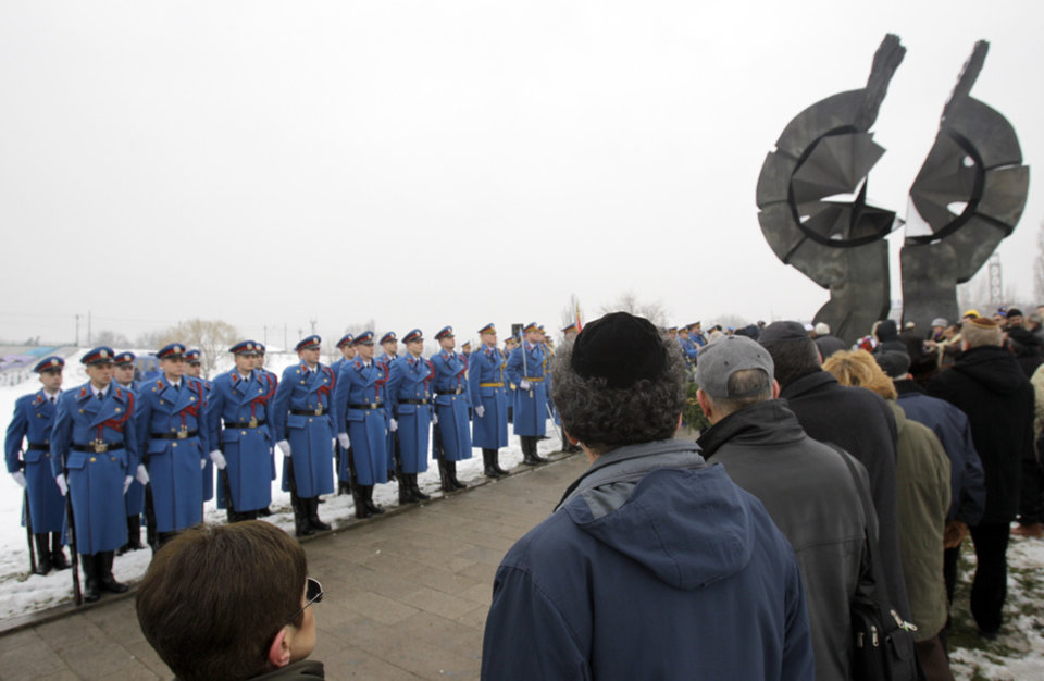 Photo - Serbian military honor guards stand to attention as people attend commemorations for victims of the Holocaust at a monument erected in the former World War II Nazi concentration camp of Sajmiste in Belgrade, Serbia, Sunday, Jan. 27, 2013. The ceremony coincided with International Holocaust Remembrance Day, which marks the liberation of the Auschwitz Nazi concentration camp on Jan. 27, 1945. (AP Photo/Darko Vojinovic)