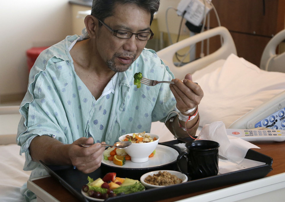 Photo - Heart patient Nhan Luong eats a heart healthy lunch of chicken fried rice, vegetables, fruit and dessert  Thursday, May 1, 2014, at Houston's Memorial Hermann Southwest Hospital. Menu changes are one way to care for an increasingly diverse population that hails from regions once not typical to the Houston area. (AP Photo/Pat Sullivan)