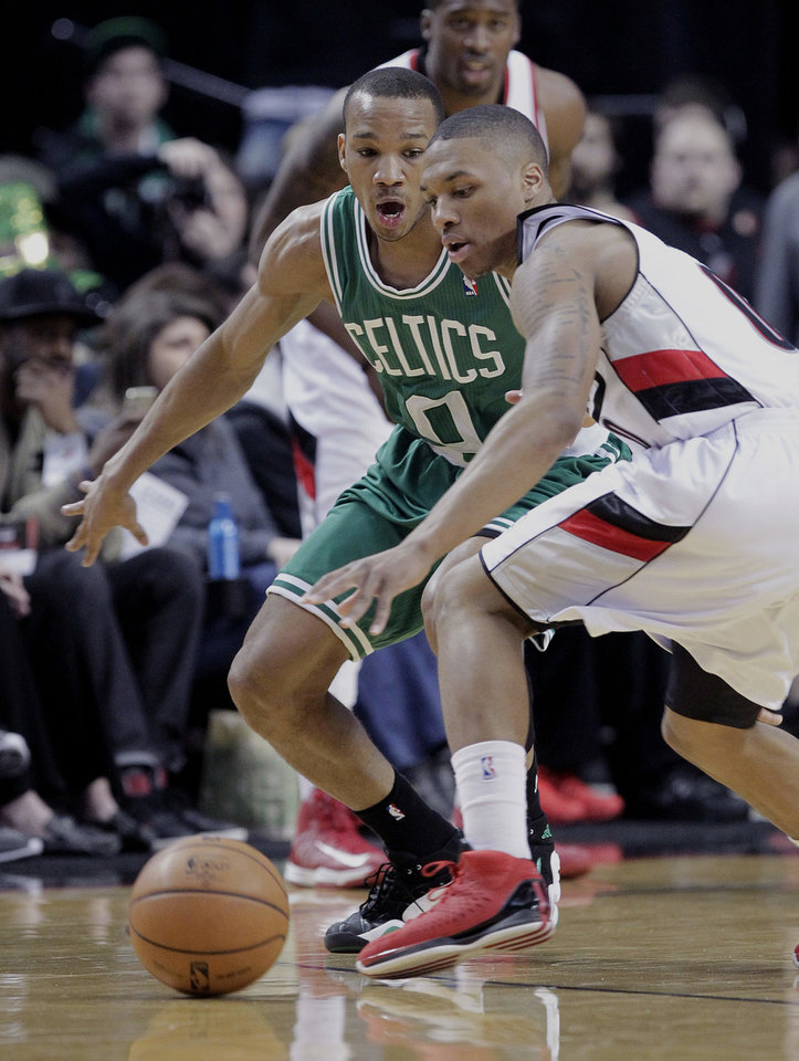 Photo - Portland Trail Blazers guard Damian Lillard, right, loses control of the ball as Boston Celtics guard Avery Bradley defends during the first quarter of an NBA basketball game in Portland, Ore., Sunday, Feb. 24, 2013. (AP Photo/Don Ryan)