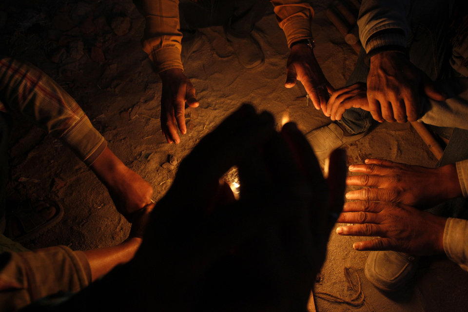 Indian laborers warm their hands near over a small fire in New Delhi, India, Tuesday, Jan. 8, 2013. North India continues to face below average weather conditions with dense fog affecting flights and trains. More than 100 people have died of exposure as northern India deals with historically cold temperatures. (AP Photo/Tsering Topgyal)