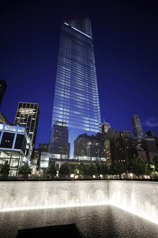 Photo - Four World Trade Center, center, rises above waterfalls at the National September 11 Memorial and Museum, Sunday, Sept. 8, 2013, in New York. Twelve years after terrorists destroyed the old World Trade Center, the new World Trade Center is becoming a reality, with a museum commemorating the attacks and two office towers where thousands of people will work set to open within the next year. (AP Photo/Mark Lennihan)