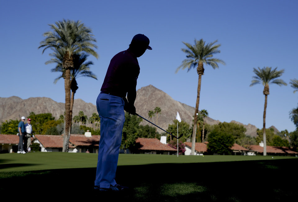 Photo - Rickie Fowler chips to the third hole during the first round of the Humana Challenge golf tournament at the La Quinta Country Club on Thursday, Jan. 16, 2014 in La Quinta, Calif. (AP Photo/Chris Carlson)