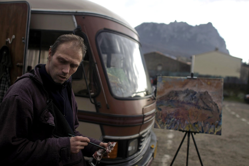 Photo - Stefano Ariu, a Dutch artist, puts the finishing touches to his painting depicting the Pic de Bugarach mountain in the town of Bugarach, France, Thursday, Dec. 20, 2012. The clock is ticking down to Dec. 21, the supposed end of the Mayan calendar, and from China to California to Mexico, thousands are getting ready for what they think is going to be a fateful day. The sleepy town of Bugarach, nestled in the French Pyrenees mountains, is bracing for the arrival of hundreds of New Age enthusiasts and UFO believers that want to witness the end of the Mayan Long Count calendar. (AP Photo/Marko Drobnjakovic)