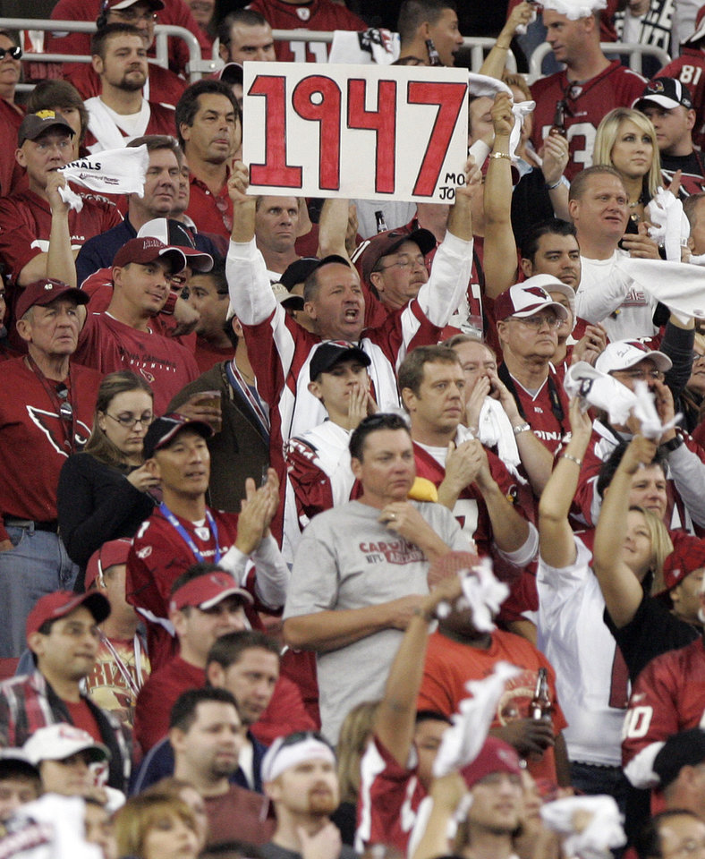 Photo - A fan holds a sign indicating the year, 1947, that the arizona Cardinals' last hosted a home playoff game, during the first quarter of an NFL wild-card playoff football game against the Atlanta Falcons Saturday, Jan.  3, 2009 in Glendale, Ariz. (AP Photo/Matt York) ORG XMIT: PNP110