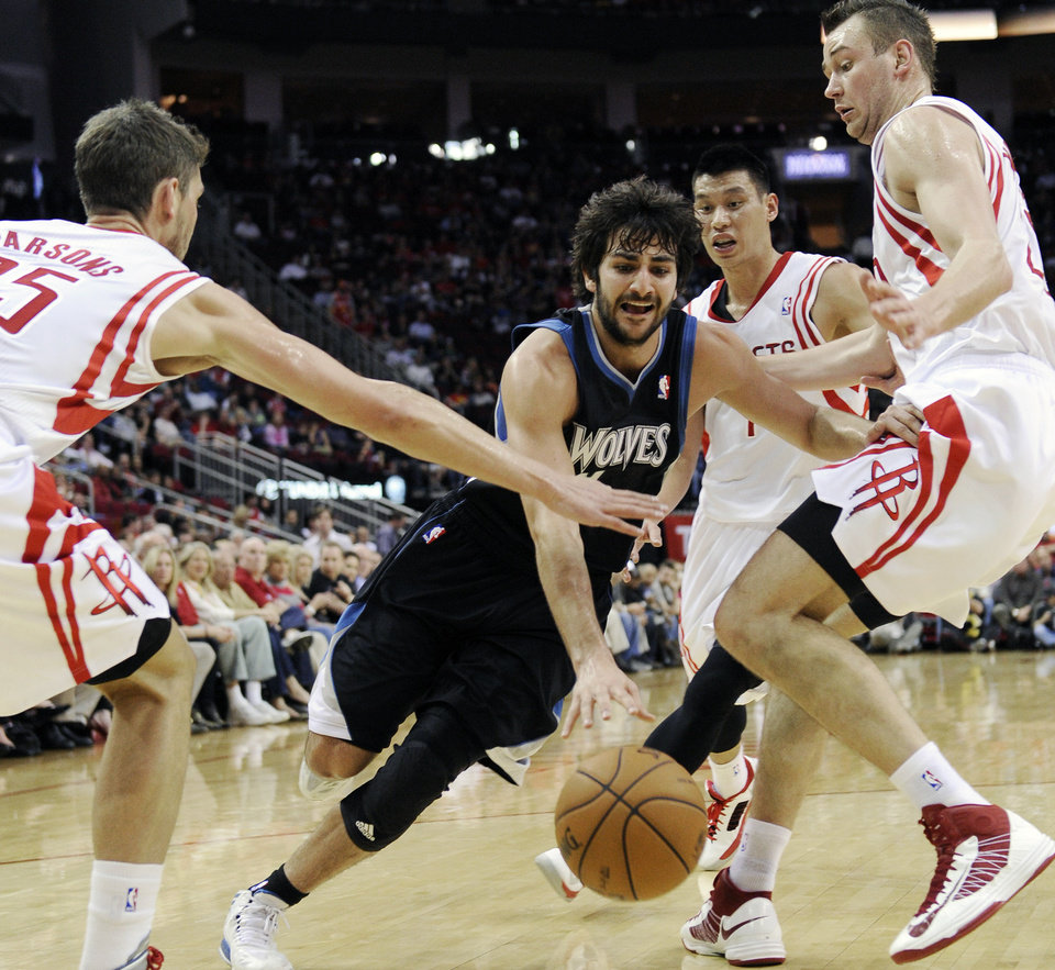 Minnesota Timberwolves' Ricky Rubio, center, drives the ball between Houston Rockets Chandler Parsons (25), Jeremy Lin (7) and Donatas Motiejunas, right, in the first half of an NBA basketball game Friday, March 15, 2013, in Houston. (AP Photo/Pat Sullivan)