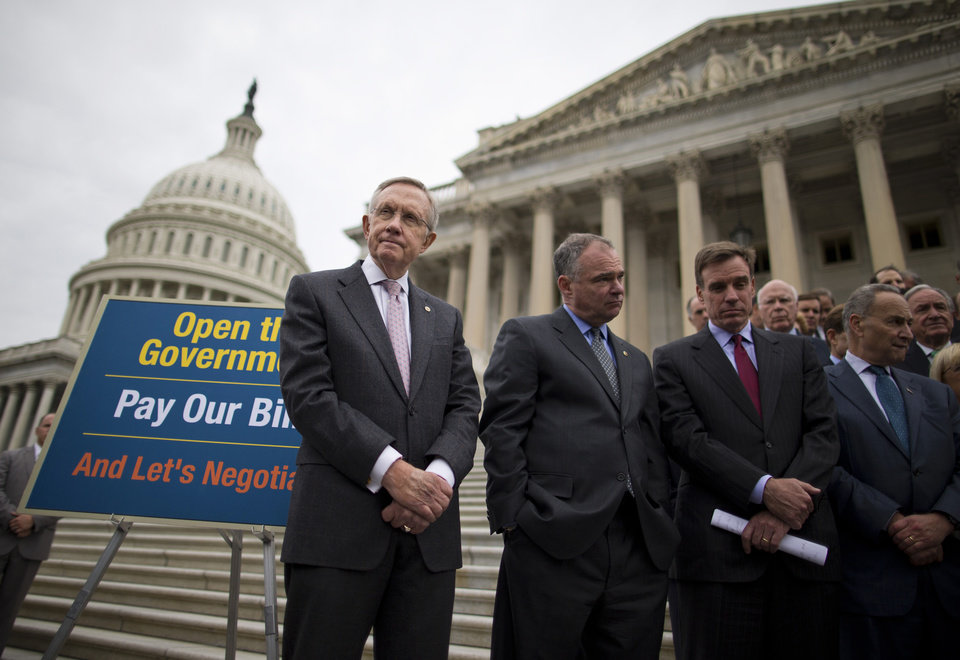 Photo - From left, Senate Majority Leader Harry Reid of Nev., Sen. Tim Kaine, D-Va., Sen. Mark Warner, D-Va., Sen. Charles Schumer, D-N.Y., and others stand on the Senate steps on Capitol Hill in Washington, Wednesday, Oct. 9, 2013, during a news conference on the ongoing budget battle. President Barack Obama was making plans to talk with Republican lawmakers at the White House in the coming days as pressure builds on both sides to resolve their deadlock over the federal debt limit and the partial government shutdown.  (AP Photo/ Evan Vucci)