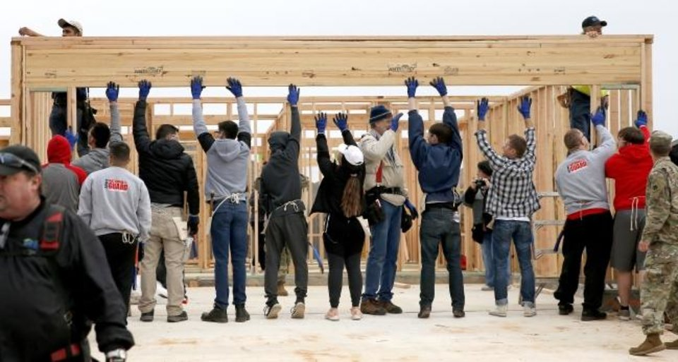 Photo -  People raise a frame on the 1,000th home by Central Oklahoma Habitat for Humanity in the Legacy Estates addition in Oklahoma City. [SARAH PHIPPS/THE OKLAHOMAN]