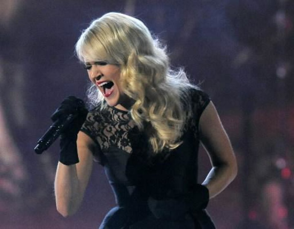 "This April 7, 2013 file photo shows Carrie Underwood performing at the 48th Annual Academy of Country Music Awards at the MGM Grand Garden Arena in Las Vegas. Underwood will pay tribute to the victims of the recent deadly tornadoes in Oklahoma in her appearance on the CMT Music Awards on Wednesday, June 5. Underwood will perform her new single ""See You Again,"" recasting it as a somber memorial with the aid of two dozen choir members from Nashville's Christ Church. (AP)"