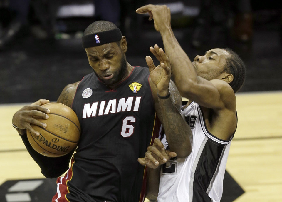 Photo - Miami Heat's LeBron James (6) is defended by San Antonio Spurs' Kawhi Leonard during the first half at Game 4 of the NBA Finals basketball series, Thursday, June 13, 2013, in San Antonio. (AP Photo/David J. Phillip)