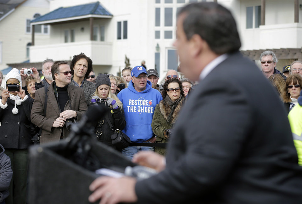 Photo - Bill Pahlck wears a Restore The Shore sweatshirt Wednesday, Jan. 9, 2013, in Belmar, N.J., as he and others listen to Gov. Chris Christie describe rebuildng plans as Belmar began construction on a 1.3-mile boardwalk to replace the walkway destroyed by Superstorm Sandy in October. Christie helped Belmar officials kick off the construction Wednesday morning. (AP Photo/Mel Evans)