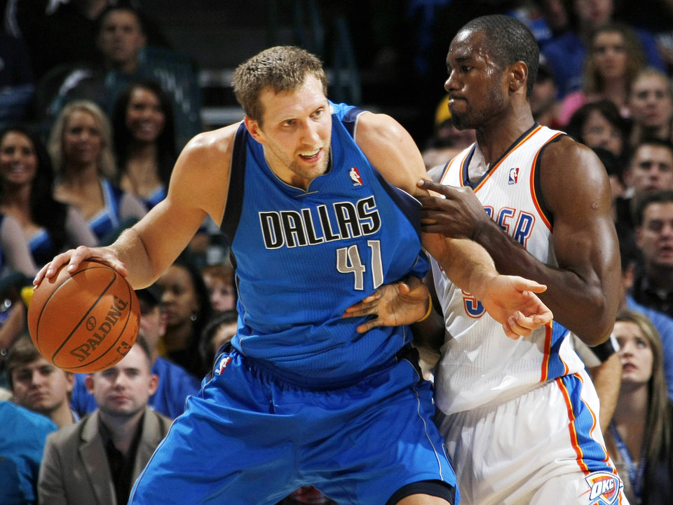 Dirk Nowitzki (41) of Dallas tries to get the ball past the defense of Oklahoma City's Serge Ibaka  (9) during the NBA basketball game between the Dallas Mavericks and the Oklahoma City Thunder at the Oklahoma City Arena in Oklahoma City, Monday, Dec. 27, 2010. Photo by Nate Billings, The Oklahoman