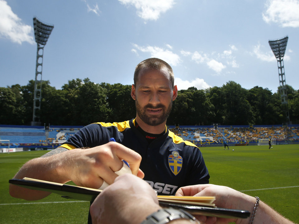 Sweden goalkeeper Johan Wiland signs an autographs for a fan prior a training session at the Euro 2012 soccer championship in Kiev, Ukraine, Wednesday, June 13, 2012. (AP Photo/Sergei Grits)