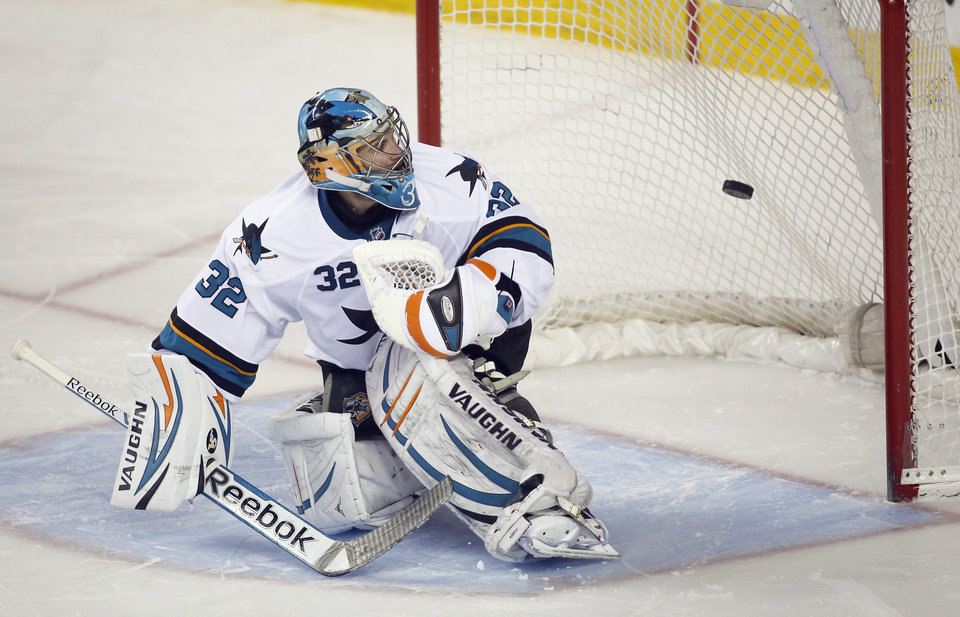 Photo - San Jose Sharks goalie Alex Stalock looks back as the winning shootout goal enters the net during overtime NHL hockey action against the Calgary Flames in Calgary, Monday, March 24, 2014. The Flames beat the Sharks 2-1 in a shootout. (AP Photo/The Canadian Press, Jeff McIntosh)