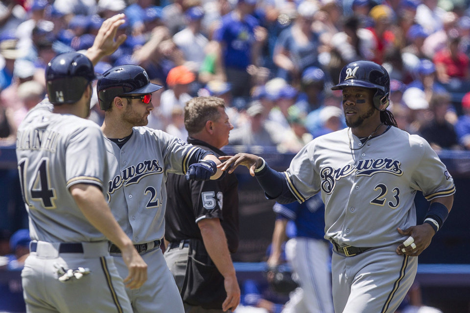 Photo - Milwaukee Brewers' Rickie Weeks, right,  and Jeff Bianchi, left, celebrate with Jonathan Lucroy after scoring on a triple by Ryan Braun during third inning interleague baseball action against the Blue Jays in Toronto on Wednesday July 2 , 2014. (AP Photo/The Canadian Press, Chris Young)