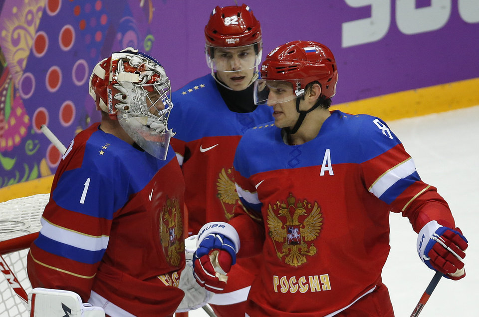 Photo - Russia forward Alexander Ovechkin, right, greets Russia goaltender Semyon Varlamov after Russia defeated Slovenia 5-2 in a men's ice hockey game at the 2014 Winter Olympics, Thursday, Feb. 13, 2014, in Sochi, Russia. (AP Photo/Mark Humphrey)