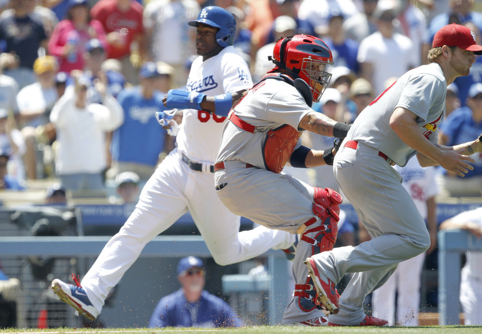 Photo - Los Angeles Dodgers' Yasiel Puig, left, scores behind St. Louis Cardinals catcher Yadier Molina, center, and starting pitcher Shelby Miller, right, taking a throw from the outfield on a single by Dodgers' Matt Kemp in the fourth inning of a baseball game on Sunday, June 29, 2014, in Los Angeles. (AP Photo/Alex Gallardo)
