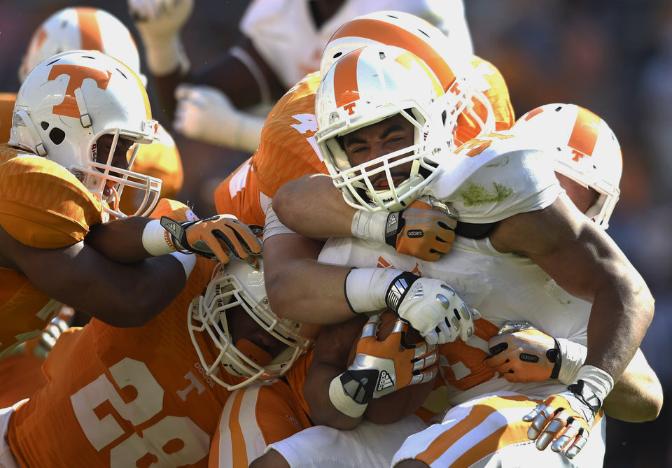 Photo - Tennessee running back Justus Pickett (31) is tackled by Tennessee defense while carrying the ball during the second half of the Orange and White game at Neyland Stadium in Knoxville, Tenn., Saturday, April 12, 2014. (AP Photo/Knoxville News Sentinel, Amy Smotherman Burgess)