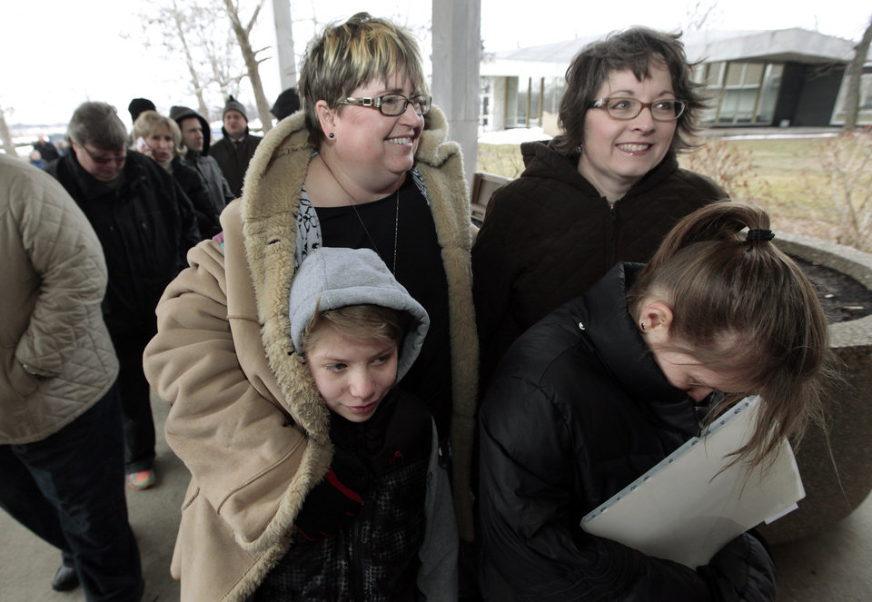Photo - Jenny Stanczyk, rear at left, and Cheryl Pine, rear at right, wait in line to apply for a marriage license at the Oakland County Clerks office with Maria , and Nina Stanczyk , front left and right, in Pontiac, Mich., Saturday, March 22, 2014. A federal judge has struck down Michigan's ban on gay marriage Friday the latest in a series of decisions overturning similar laws across the U.S. Some counties plan to issue marriage licenses to same-sex couples Saturday, less than 24 hours after a judge overturned Michigan's ban on gay marriage. (AP Photo/Paul Sancya)