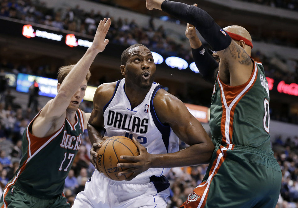 Dallas Mavericks' Elton Brand, center, fights for a shot opportunity against Milwaukee Bucks' Mike Dunleavy (17) and Drew Gooden, right, during the second half of an NBA basketball game Tuesday, Feb. 26, 2013, in Dallas. The Bucks won 95-90. (AP Photo/Tony Gutierrez)