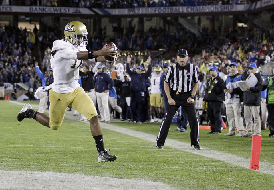 Photo - UCLA quarterback Brett Hundley runs into the end zone on a 5-yard touchdown run against Stanford during the first half of the Pac-12 championship NCAA college football game in Stanford, Calif., Friday, Nov. 30, 2012. (AP Photo/Tony Avelar)