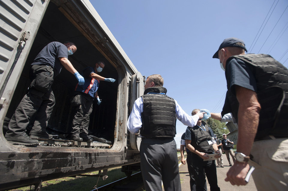 Photo - Deputy head of the OSCE mission to Ukraine Alexander Hug, center back to the camera, speaks to a member of Netherlands' National Forensic Investigations Team on the platform as a refrigerated train loaded with bodies of the passengers departs the station in Torez, eastern Ukraine, 15 kilometers (9 miles) from the crash site of Malaysia Airlines Flight 17, Monday, July 21, 2014. Another 21 bodies have been found in the sprawling fields of east Ukraine where Malaysia Airlines Flight 17 was downed last week, killing all 298 people aboard. International indignation over the incident has grown as investigators still only have limited access to the crash site and it remains unclear when and where the victims' bodies will be transported. (AP Photo/Evgeniy Maloletka)