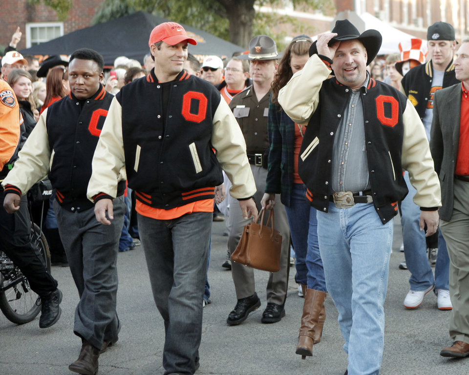 Photo - ALUMNI HALL OF FAME / INDUCT / INDUCTED / INDUCTEE / INDUCTION: Barry Sanders, Robin Ventura and Garth Brooks wave to the crowd during the walk to the stadium before the college football game between Oklahoma State University (OSU) and the University of Missouri (MU) at Boone Pickens Stadium in Stillwater, Okla. Saturday, Oct. 17, 2009.  Photo by Doug Hoke, The Oklahoman ORG XMIT: KOD