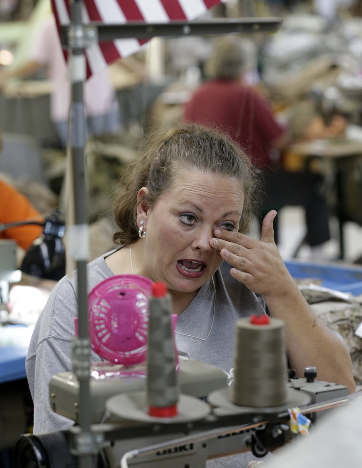 In this Wednesday, Oct. 10, 2012 photo, apparel worker Misti Keeton wipes tears from her eyes as she talks about the possibility of losing her job to a convict, at American Power Source in Fayette, Ala. Keeton was at work sewing military apparel. Her employer, American Power Source, is laying off about 50 workers at her plant and another one in Columbus, Miss., after losing a contract to make Air Force exercise garb to Unicor. �I�m terrified,� Keeton said as she fed camouflage cloth through a machine with one hand and wiped away tears with the other. �I�ve got two teenagers at home. I don�t know what I�m supposed to say to them if I lose this job. I don�t know what I�m supposed to feed them.� (AP Photo/Dave Martin)