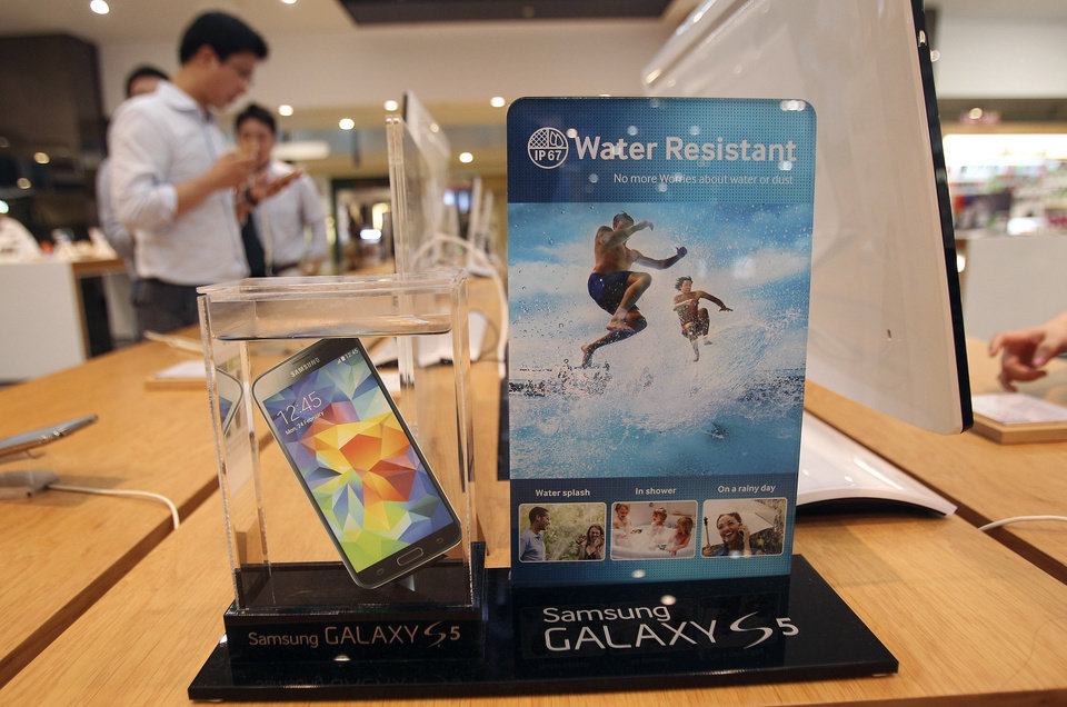 Photo - A Samsung Electronics' Galaxy S5 smartphone is displayed at the company's showroom in Seoul, South Korea, Thursday, July 31, 2014. Samsung Electronics Co. reported a bigger-than-expected fall in second quarter profit on Thursday and said it was uncertain if earnings from its handset business would improve in the current quarter.(AP Photo/Ahn Young-joon)
