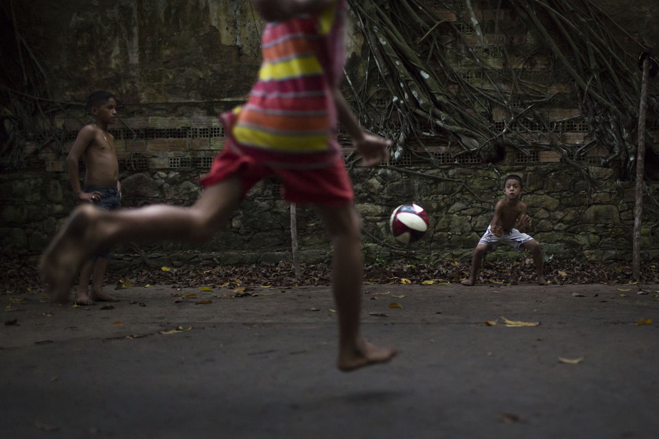 Photo - In this May 21, 2014 photo, A boy kicks a penalty during a soccer match in the ruins of Paricatuba, near Manaus, Brazil. Children of the tiny village of Paricatuba, which grew up around the villa, use the ruins as a spot for energetic games of barefoot soccer or to scare themselves silly. Teenagers come here to make out, and older people to get drunk. (AP Photo/Felipe Dana)