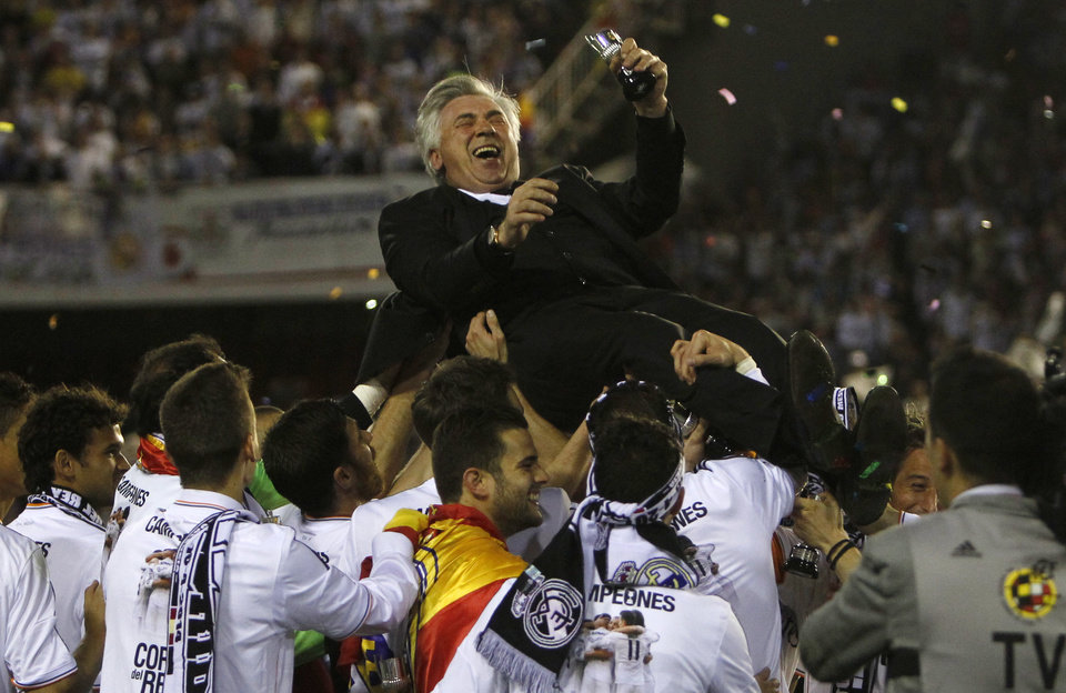 Photo - Real's coach Carlo Ancelotti is lifted by team players after Real Madrid won the final of the Copa del Rey between FC Barcelona and Real Madrid at the Mestalla stadium in Valencia, Spain, Wednesday, April 16, 2014. (AP Photo/Alberto Saiz)