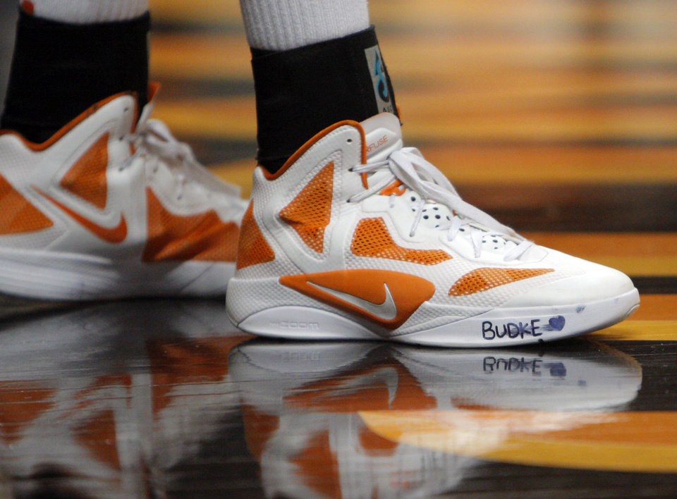 Photo - An Oklahoma State player wears late coach Kurt Budke's name on her sneaker during an NCAA college basketball game  against Coppin State in Stillwater, Okla., Saturday, Nov. 26, 2011. Budke, the head coach for the women's basketball team, and Miranda Serna, his assistant, were killed Thursday when the single-engine plane transporting them on a recruiting trip crashed in steep terrain in Arkansas.