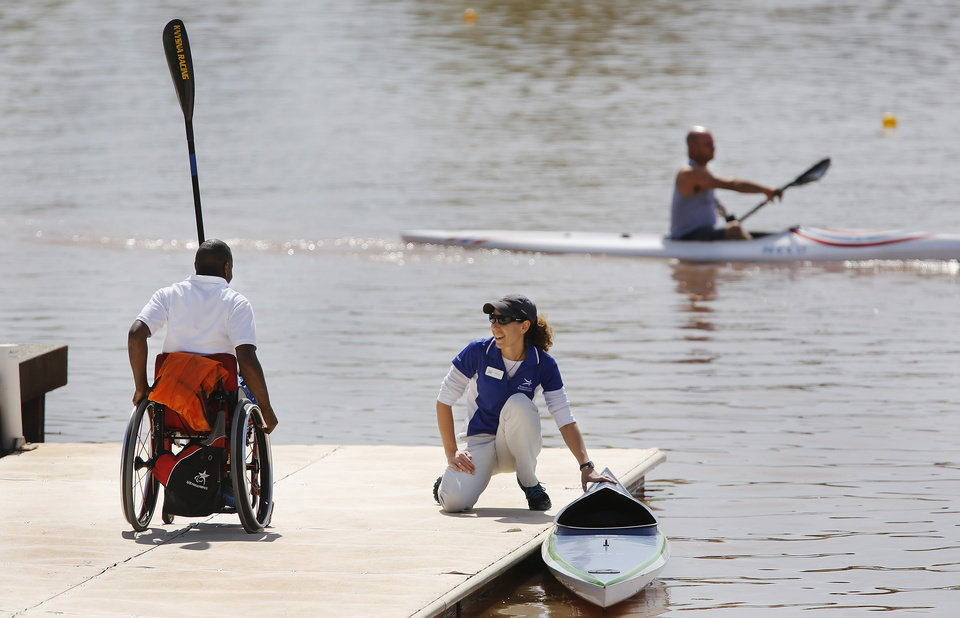 Sherry Andrusiak holds the kayak in place as Shad Isaac, 22,  rolls his wheelchair along the dock during a morning practice session for this weekend's USA Canoe/Kayak Trials for Flatwater Sprint.  Photo taken on the Oklahoma River, on  Thursday, April 25, 2013. Photo  by Jim Beckel, The Oklahoman.