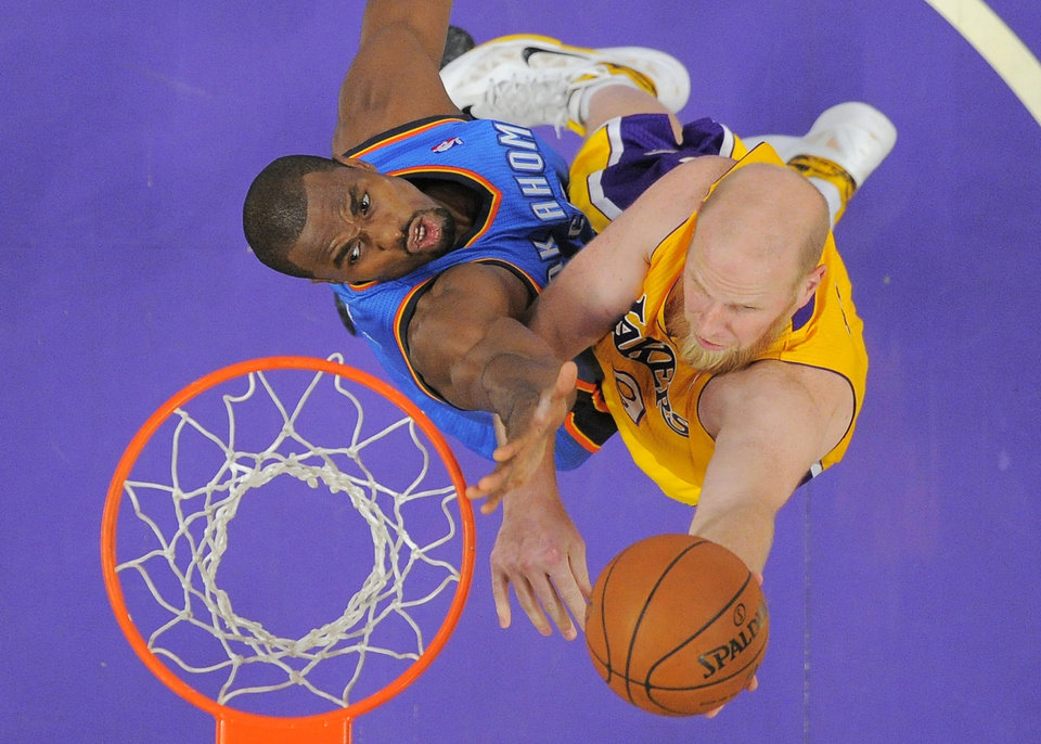Photo - Los Angeles Lakers center Chris Kaman, right, puts up a shot as Oklahoma City Thunder forward Serge Ibaka, of Congo, defends during the first half of an NBA basketball game Thursday, Feb. 13, 2014, in Los Angeles. (AP Photo/Mark J. Terrill)