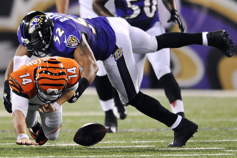 Photo - FILE - In this Sept. 10, 2012, file photo, Cincinnati Bengals quarterback Andy Dalton (14) fumbles the ball as he is sacked by Baltimore Ravens linebacker Ray Lewis in the second half of an NFL football game in Baltimore. Baltimore recovered the ball on the play. Lewis announced, Wednesday, Jan. 2, 2013, that he will end his brilliant NFL career after the Ravens complete their 2013 playoff run. (AP Photo/Gail Burton, File)