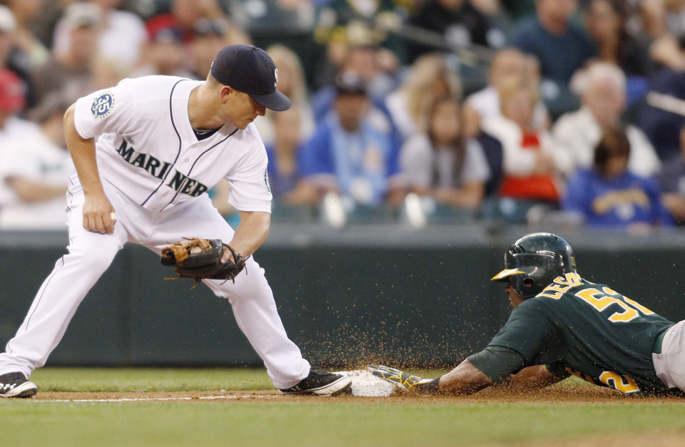 Photo -   Oakland Athletics' Yoenis Cespedes tags third for a steal before the tag from Seattle Mariners third baseman Kyle Seager during the fourth inning of a baseball game in Seattle on Saturday, Sept. 8, 2012. (AP Photo/John Froschauer)