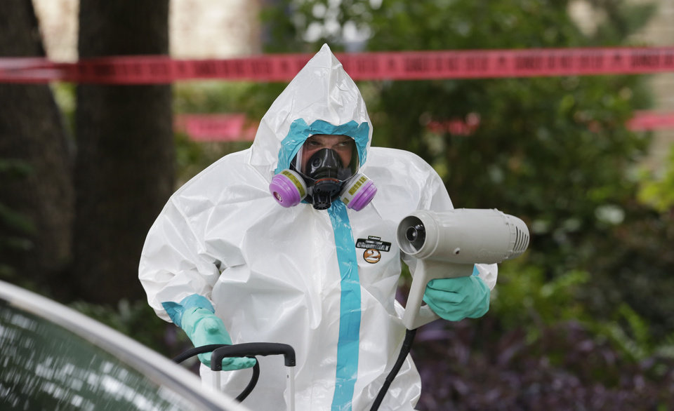 Photo - A hazmat worker cleans outside the apartment building of a hospital worker, Sunday, Oct. 12, 2014, in Dallas. The Texas health care worker, who was in full protective gear when they provided hospital care for Ebola patient Thomas Eric Duncan, who later died, has tested positive for the virus and is in stable condition, health officials said Sunday. (AP Photo/LM Otero)
