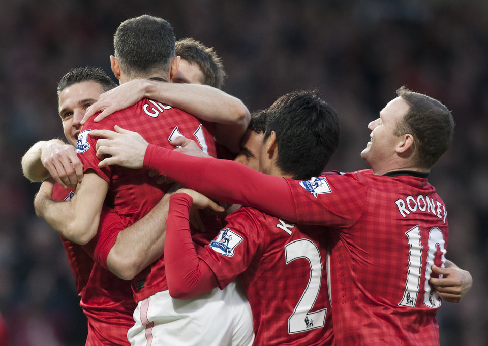 Manchester United's Robin van Persie, obscured extreme left, celebrates with teammates after scoring against Aston Villa during their English Premier League soccer match at Old Trafford Stadium, Manchester, England, Monday April 22, 2013. (AP Photo/Jon Super)