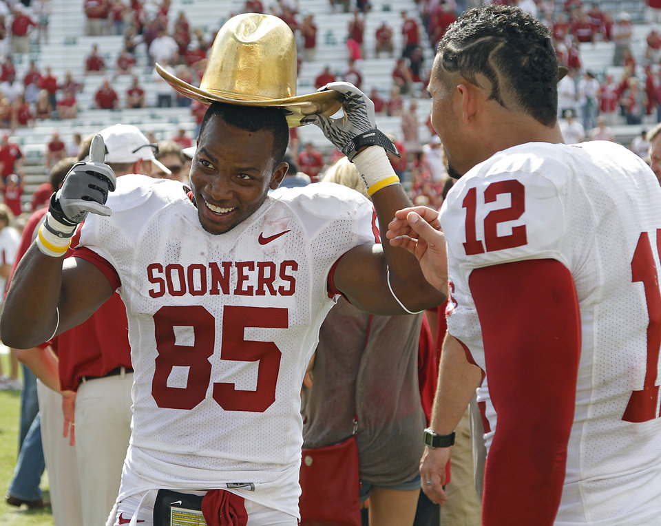 Photo - Oklahoma's Ryan Broyles (85) and Travis Lewis (12) celebrate with the Golden Hat trophy after the Sooners 55-17 win over Texas during the Red River Rivalry college football game between the University of Oklahoma Sooners (OU) and the University of Texas Longhorns (UT) at the Cotton Bowl in Dallas, Saturday, Oct. 8, 2011. Photo by Chris Landsberger, The Oklahoman