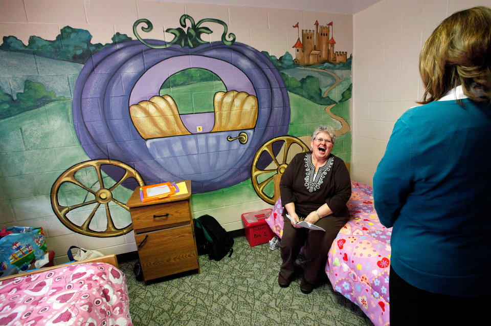 Patricia Rowe, supervisor and trainer at the Pauline E. Mayer Children's Shelter, sits near a colorful mural of a fairy tale scene that makes the room one of the most popular for young girls.