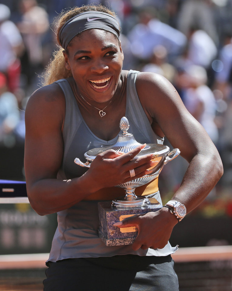 Photo - Serena Williams smiles as she holds the trophy after winning the final match against Italy's Sara Errani at the Italian open tennis tournament in Rome, Sunday, May 18, 2014. Serena Williams kept the crowd from being a factor in a 6-3, 6-0 victory over 10th-seeded Sara Errani to win the Italian Open for the third time Sunday. (AP Photo/Gregorio Borgia)