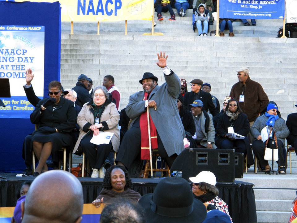 Photo - North Carolina NAACP President William Barber waves to the crowd as he waits to speak at the King Day celebration on Monday, Jan. 20, 2014, in Columbia, S.C. Barber was invited to speak about social justice. (AP Photo/Jeffrey Collins)