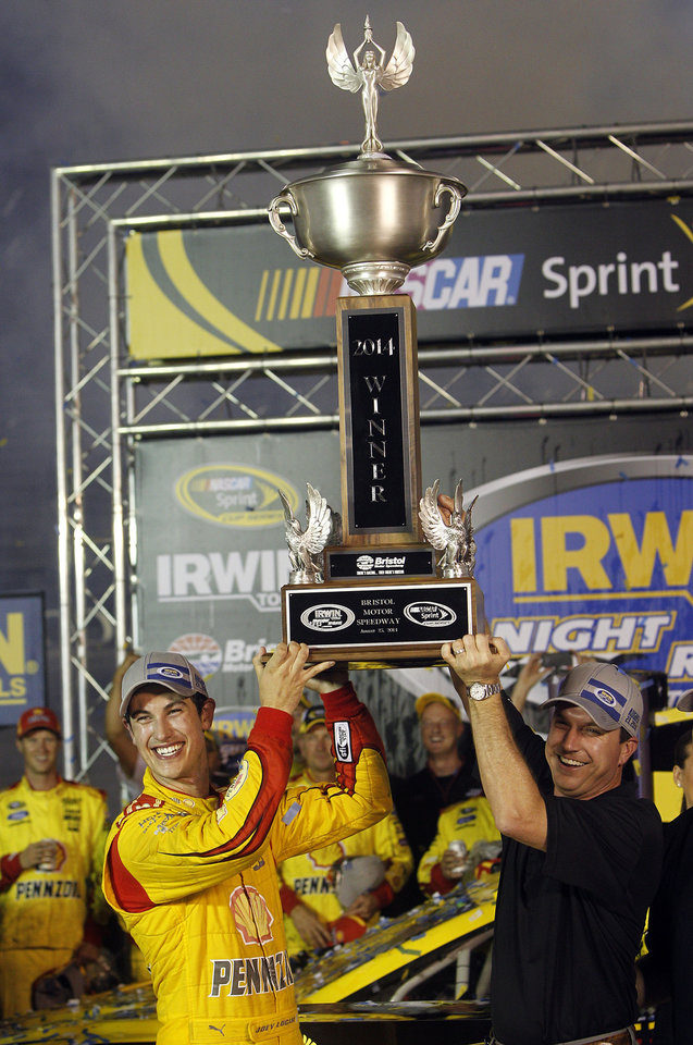 Photo - Joey Logano hoists the trophy with Jerry Caldwell, General Manager of Bristol Motor Speedway after winning a NASCAR Sprint Cup Series auto race at Bristol Motor Speedway on Saturday, Aug. 23, 2014, in Bristol, Tenn. (AP Photo/Wade Payne)