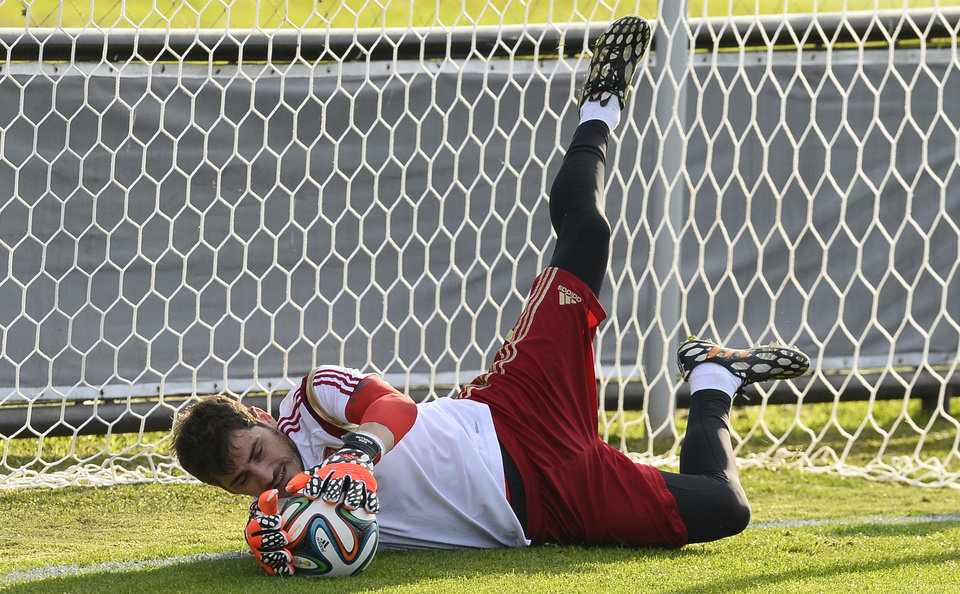 Photo - Spain's goalkeeper Iker Casillas saves a ball during a training session at he Atletico Paranaense training center in Curitiba, Brazil, Saturday, June 14, 2014. Spain will play in group B of the Brazil 2014 World Cup. (AP Photo/Manu Fernandez)