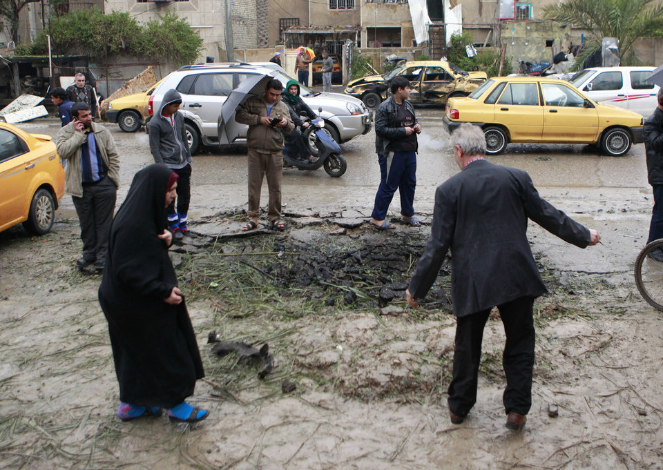 Photo - Iraqi civilians inspect a crater caused by a car bomb in a commercial area in the northern Hurriyah neighborhood of Baghdad, Iraq, Monday, Feb. 3, 2014. Iraqi officials say car bombings on Monday in and near Baghdad have killed and wounded scores of people. (AP Photo/Hadi Mizban)