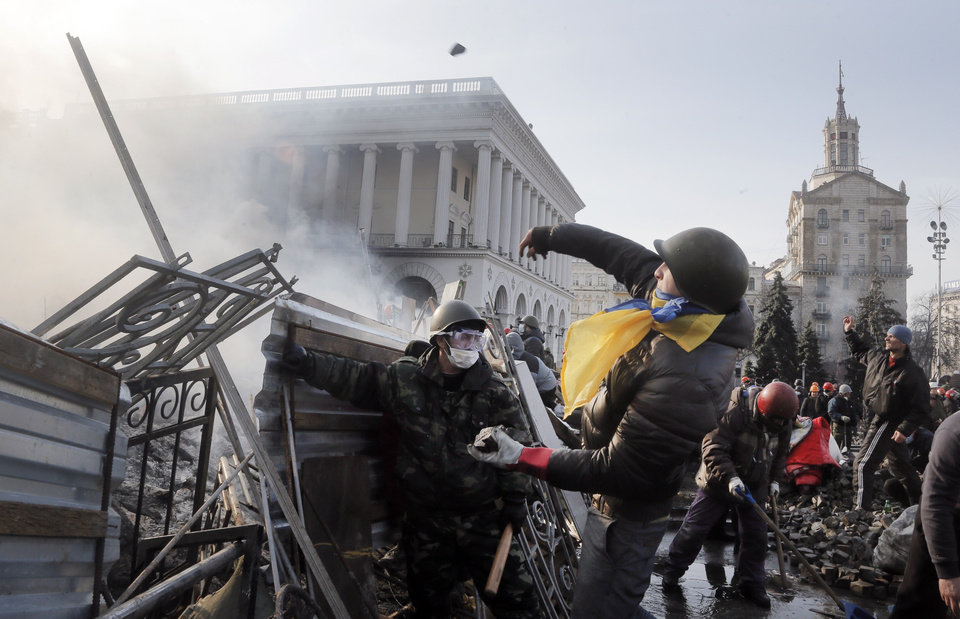 Photo - An anti-government protester throws a stone during clashes with riot police in Kiev's Independence Square, the epicenter of the country's current unrest, Kiev, Ukraine, Wednesday, Feb. 19, 2014. The deadly clashes in Ukraine's capital have drawn sharp reactions from Washington, generated talk of possible European Union sanctions and led to a Kremlin statement blaming Europe and the West.  (AP Photo/Efrem Lukatsky)