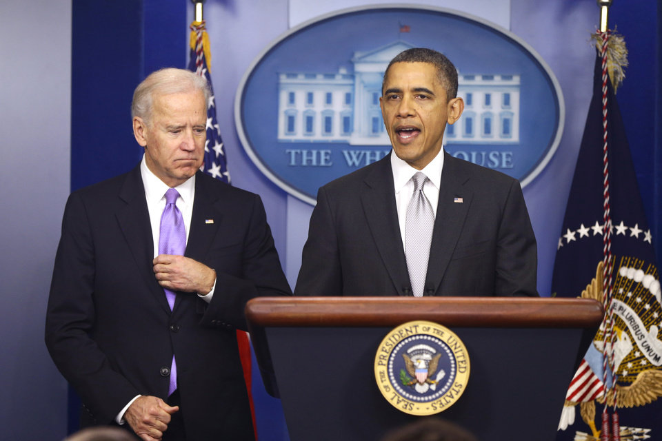 Photo - President Barack Obama stands with Vice President Joe Biden as he makes a statement in the Brady Press Briefing Room about policies he will pursue following the Newtown, Ct., school shootings, Wednesday, Dec. 19, 2012, at the White House in Washington. (AP Photo/Charles Dharapak)