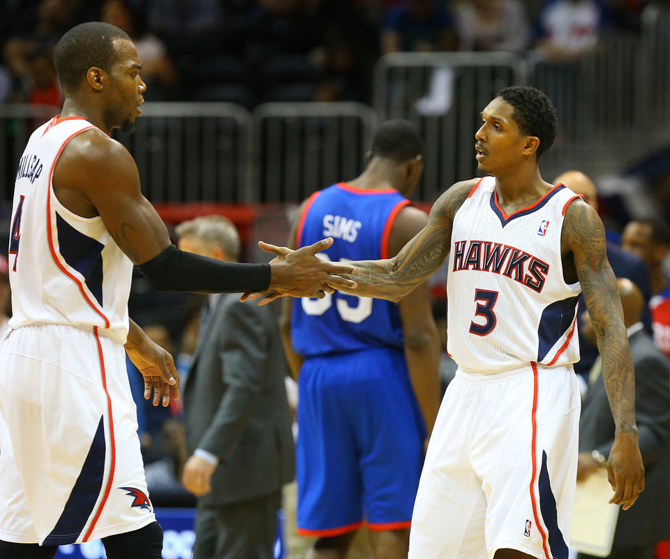 Atlanta Hawks guard Lou Williams, right, celebrates hitting one of his three-pointers down the stretch with teammate Paul Millsap, left. on the way to a 103-95 victory over the Sixers in an NBA basketball game on Monday, March 31, 2014, in Atlanta.   (AP Photo/Atlanta Journal-Constitution, Curtis Compton)