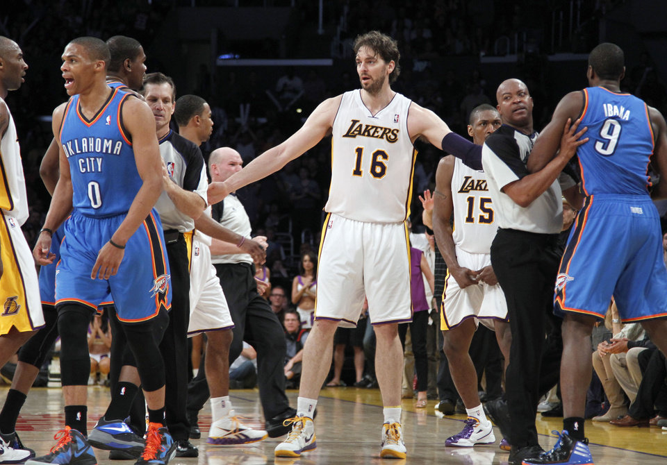 The Los Angeles Lakers Pau Gasol (16), of Spain, stands between Oklahoma City Thunder and other players after Lakers' Metta World Peace (15) was called for a double fragrant foul and ejected from the game in the first half of an NBA basketball game, Sunday, April 22, 2012, in Los Angeles. (AP Photo/Reed Saxon) ORG XMIT: LAS101